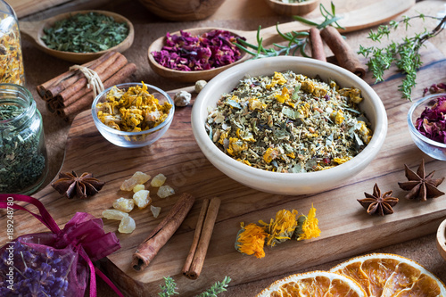 A mix of dried and fresh herbs on a wooden table Canvas Print