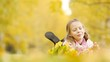 Portrait of adorable little girl with yellow leaves bouquet in fall. Beautiful
