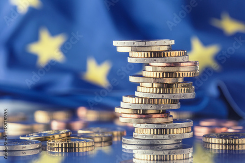 Euro money.Euro Flag.Euro currency.Coins stacked on each other in different positions. European union flag