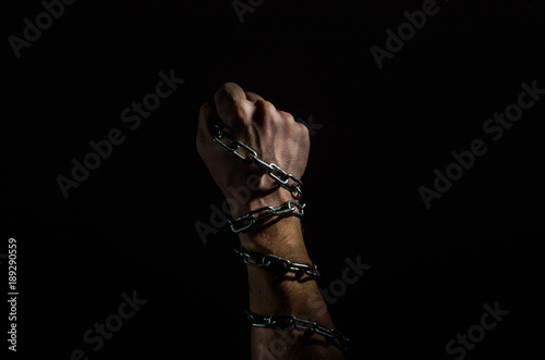 Photo Hands are chained in chains isolated on black background