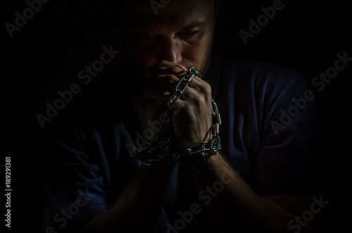 Tablou Canvas Repented man prisoner with his hands shackled in chains on a dark background