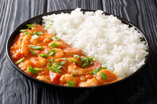 American cuisine: spicy gumbo with prawns, sausage and rice close-up on a plate. horizontal