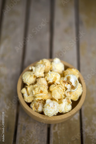 Salted Popcorn In Round Wooden Bowl On Wooden Table Background
