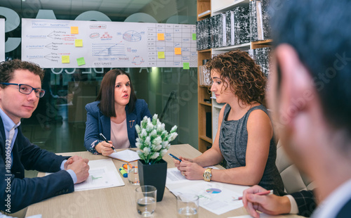 Businesswoman talking in a business meeting to teamwork sitting at table in comp Canvas Print