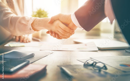 Fotomural  Businessman and businesswoman shaking hands above desk