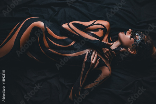 Obraz Beautiful girl with painted body and black mask in her face lies on bed. Body art. - fototapety do salonu