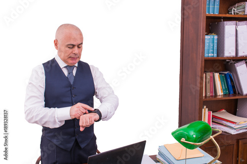 Fotografie, Obraz  A businessman uses smartwacth pic, at desk, at work.