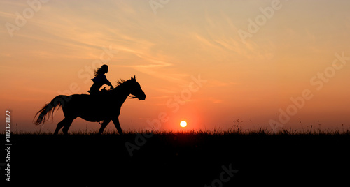 Horseback woman riding on galloping horse with red rising sun on horizon. Beautiful colorful sunset background with equine and girls silhouette horse hiking