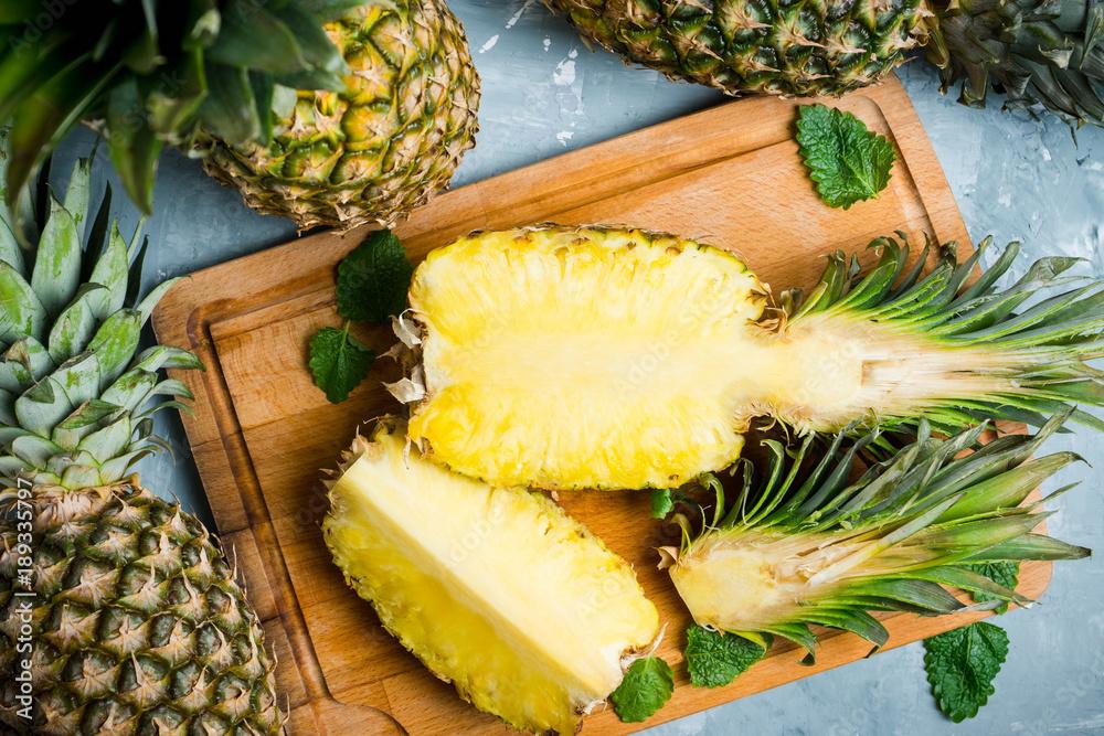 Fototapeta Fresh ripe pineapples on the rustic background. Selective focus.