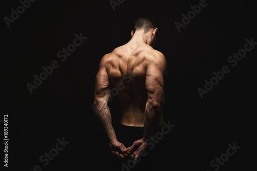 Obraz Unrecognizable man shows strong back muscles closeup - fototapety do salonu