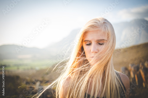 Poster Natuur Portrait of a beautiful blond female model in a natural setting with stunning back light