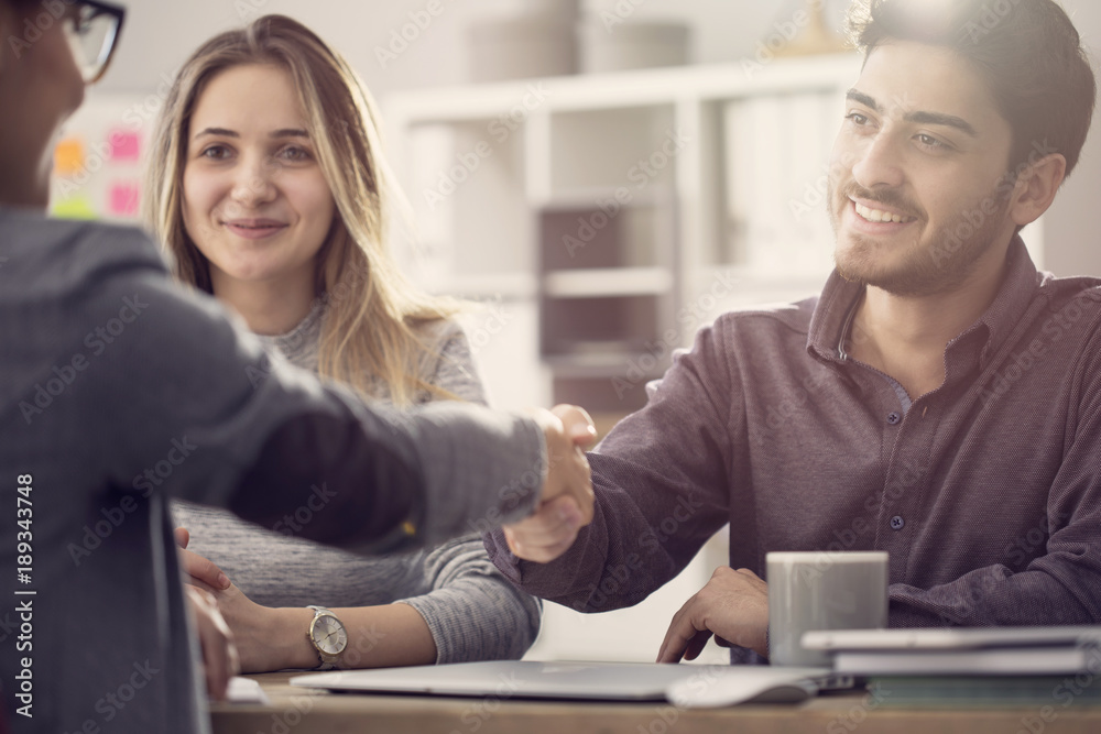 Fototapeta Young couple shaking hands with a female agent
