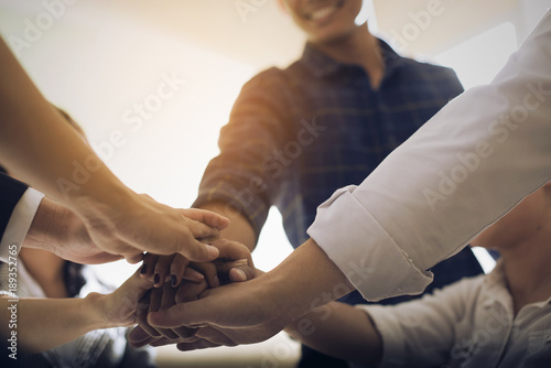 Businessmen stack hands together to express their unity.