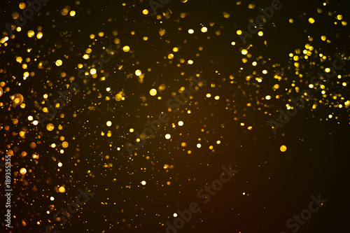 christmas gold sparkle glitter explosion dust particles background with bokeh gold holiday happy new year
