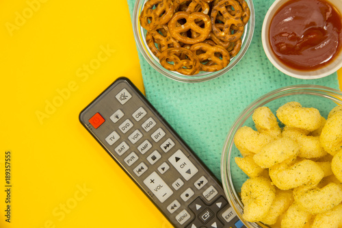Weekend, Leisure, Lifestyle Concept A remote control, salty pretzels, corn chips and ketchup on a bright one-colore yellow background Canvas Print