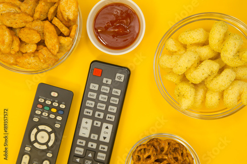 Fotografie, Tablou  Weekend, Leisure, Lifestyle Concept Two remote controls, salty pretzels, bread crumbs, corn chips and ketchup on a bright one-colore yellow background