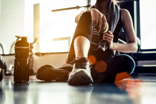Fotobehang Fitness Sport woman sitting and resting after workout or exercise in fitness gym with protein shake or drinking water on floor. Relax concept. Strength training and Body build up theme. Warm and cool tone