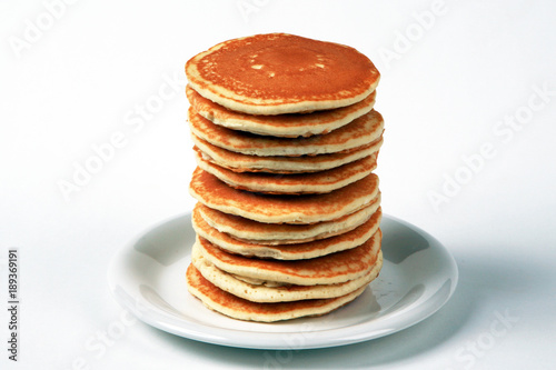 Fotografie, Obraz  Tall stack of pancakes set against a white background