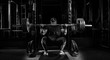 Leinwanddruck Bild - Professional athlete sits with a barbell on his shoulders and prepares to stand with her.