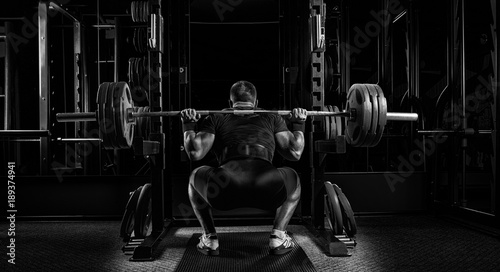 Obraz na plátne  Professional athlete sits with a barbell on his shoulders and prepares to stand with her