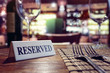 canvas print picture - Reserved sign on restaurant table with bar background