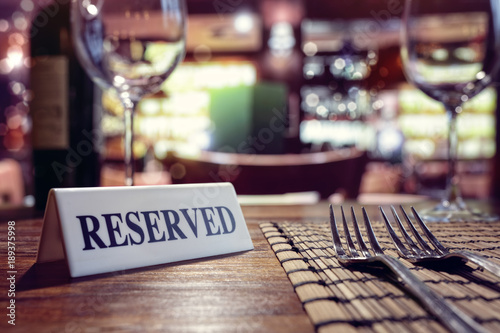 In de dag Restaurant Reserved sign on restaurant table with bar background