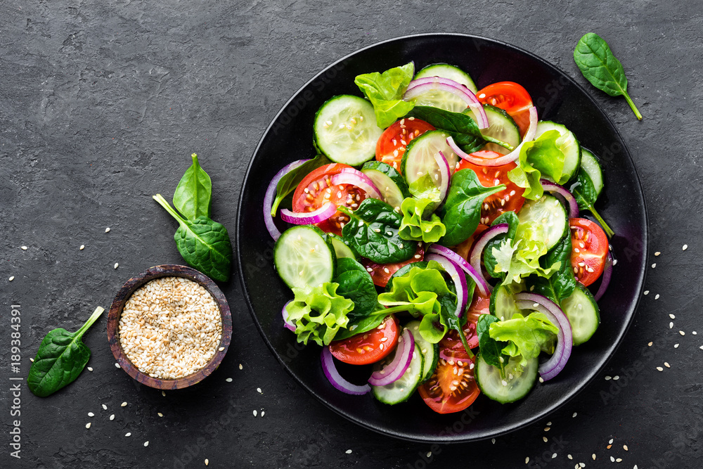 Fototapety, obrazy: Healthy vegetable salad of fresh tomato, cucumber, onion, spinach, lettuce and sesame on plate. Diet menu. Top view.