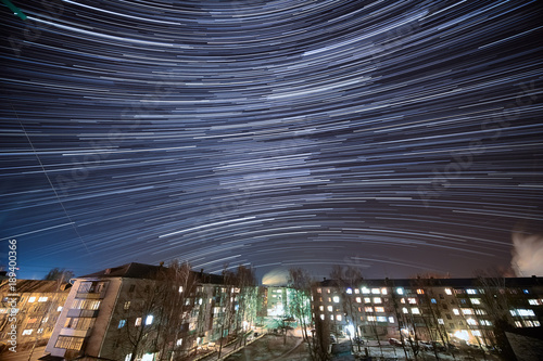 Poster  Night Star Trails Over Rural Town at winter