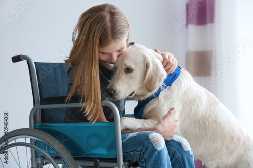 Girl in wheelchair with service dog indoors Wallpaper Mural