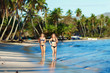 two slender girls running on sandy tropical beach