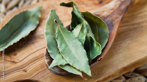 Suche liście laurowe - aromatyczne indyjskie przyprawy na drewnianej łyżce, makro.