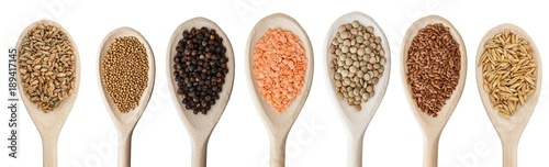 Various grain products, spices and lentils on wooden spoons isolated on white.