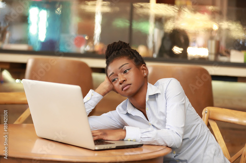 Tired young girl looking at laptop Fototapeta