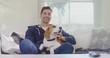 Smiling man sitting on sofa stroking his pet dog while watching television