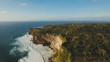 Aerial view of sea rocky coast with surf the waves, Bali,Indonesia, Pura Uluwatu cliff. Waves crushing rocky shore. Ocean with waves and rocky clif. Seascape, rocks, ocean. 4K video. Travel concept