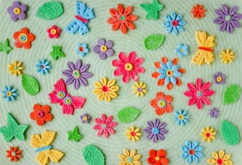Easter colorful background with edible butterfly, flowers and leaves from sugar paste
