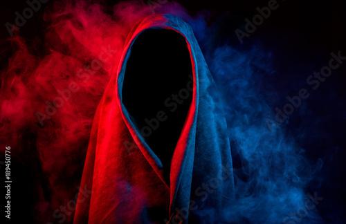 Fotografía  mysterious dark silhouette hidden by colorful smoke on black background