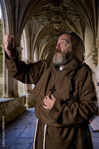 Fotografía Monk praying in the cloister of a monastery.
