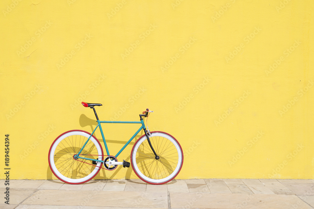 Fototapeta A City bicycle fixed gear on yellow wall