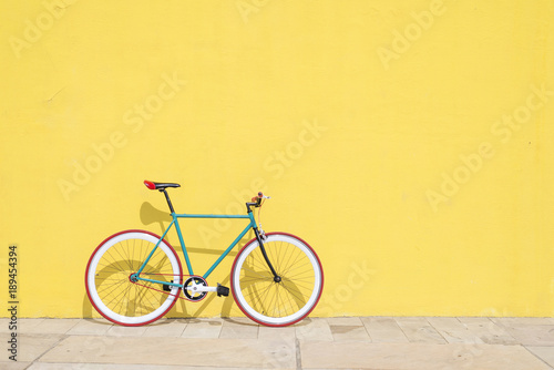 Foto op Plexiglas Fiets A City bicycle fixed gear on yellow wall