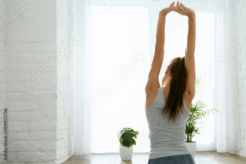 Fényképezés Woman Stretching Hands Near Window In Morning