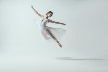 elegantna baletana u bijeloj haljini skačući u studiju, izolirana na bijeloj