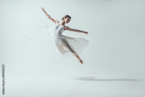 Fotografiet elegant ballet dancer in white dress jumping in studio, isolated on white