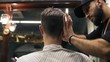 Back view of a young man getting his hair cut sitting in the chair at the