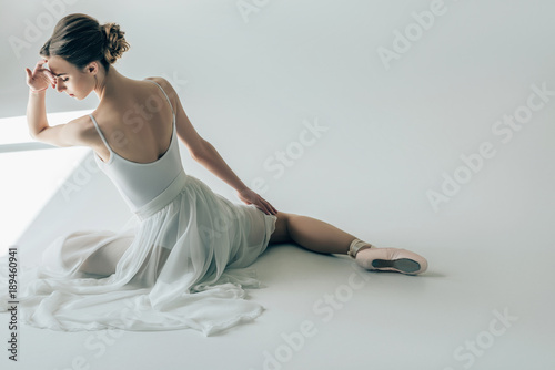 Photo back view of elegant ballerina sitting in white dress and ballet shoes