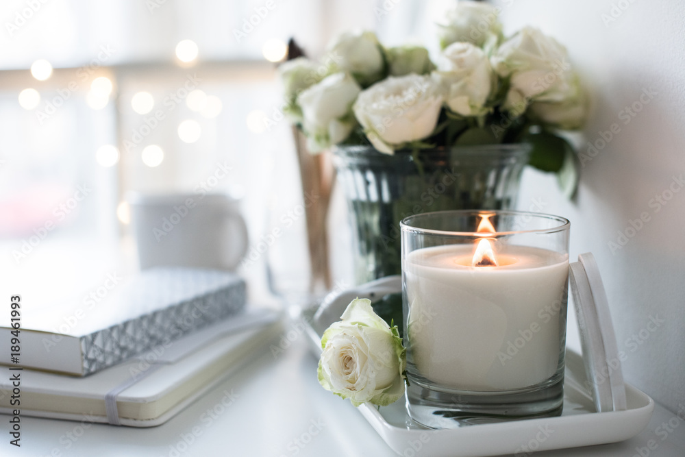 Fototapeta White room interior decor with burning hand-made candle and bouq