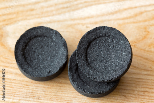 Photo  Black round disc of Arabian charcoals to burn aromatic incense, resin gum on wood background