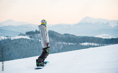fototapeta na szkło Female snowboarder enjoying skiing in mountains in the evening on the slope at winter ski resort in the mountains copyspace stunning view scenery landscape recreation concept