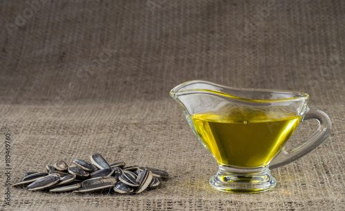 Fototapeta Sunflower seed oil in a glass gravy boat and a handful of sunflower seeds on the background of burlap. obraz