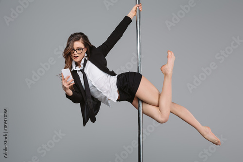 Fotografie, Obraz  young businesswoman in eyeglasses using smartphone and exercising with pole on g